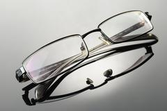 modern glassess on a reflective surface - stock photo