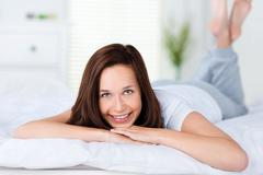 Smiling woman lying on her bed Stock Photos
