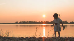 Silhouette of a girl playing on shore Stock Footage