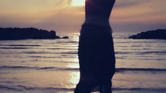Dressed woman in love runs to her man into the sea - hugs and kisses - sunset Stock Footage