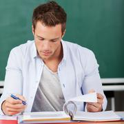 Thoughtful man with folder in front of chalkboard Stock Photos