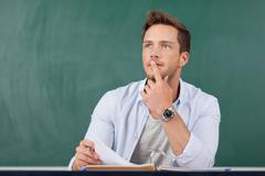 thoughtful man with folder in front of chalkboard - stock photo