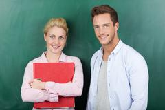 Portrait of business couple against green background Stock Photos