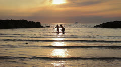 a boy and girl into the sea at sunset chases and jokes  with water - stock footage