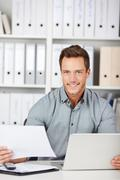 Stock Photo of man in office with laptop and documents