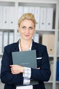 Confident businesswoman holding folder Stock Photos