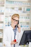 Portrait of smiling pharmacist on phone at drugstore Stock Photos