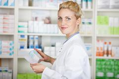 pharmacist with prescription at drugstore - stock photo