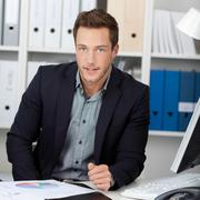 smart businessman with graphs at office desk - stock photo