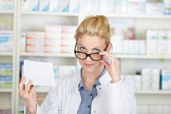 pharmacist with prescription looking over glasses - stock photo