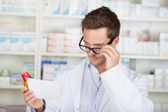 Pharmacist with prescription at drugstore Stock Photos