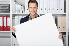 businessman holding blank sign at office - stock photo