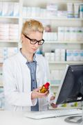 pharmacist checking prescription bottle at drugstore - stock photo