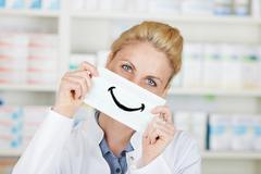 Female pharmacist holding happy smiley Stock Photos