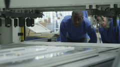 Male machine operators in a factory checking the process Stock Footage