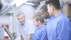 Happy male factory staff of mixed ethnicity with their line manager Stock Footage