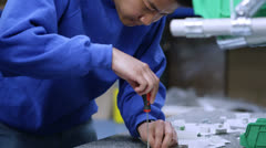 Young Asian factory worker concentrating on his work - stock footage