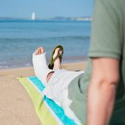 man with plaster relaxing on beach - stock photo
