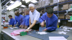 Time lapse of workers on an assembly line making lighting components - stock footage