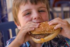 boy with hamburger - stock photo