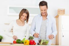 couple preparing salad in the kitchen - stock photo