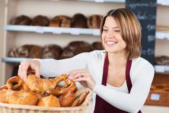 woman in the bakery filling a basket with bread - stock photo