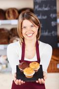 female bakery worker with fresh muffins - stock photo