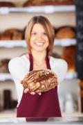 Friendly bakery assistant with bread Stock Photos