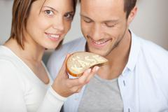 smiling couple holding a slice of bread and cheese - stock photo