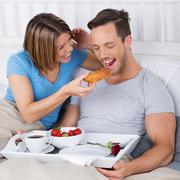 Laughing couple enjoying breakfast in bed Stock Photos