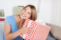 pretty woman shaking a large present - stock photo