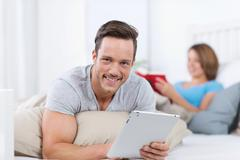 Smiling young man relaxing with a tablet-pc Stock Photos