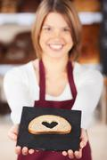 worker displaying bread with a heart - stock photo