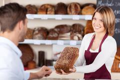Bakery assistant selling bread Stock Photos
