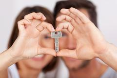young couple holding a house key together - stock photo