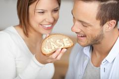 happy couple holding a slice of bread and cheese - stock photo