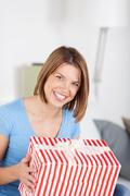 excited woman with a large striped gift - stock photo