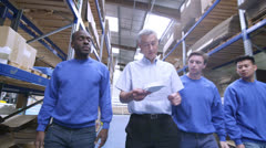 Team of male workers in warehouse or factory Stock Footage