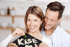 young couple holding a stone slab with cheese - stock photo