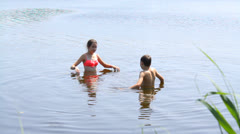 Two kids enjoy a beautiful day in the lake Stock Footage