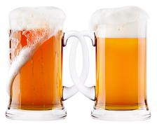 Two beer mugs being attached to each other - stock photo
