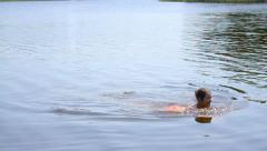 Attractive girl learns to swim in great summer day Stock Footage
