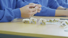 Team of male workers in a factory assembling electrical fittings Stock Footage