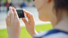 Woman filming mobile cell phone in city park - stock footage