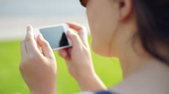 Woman text messaging mobile phone in city park - stock footage