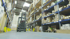 Forklift truck driver in a factory or warehouse driving between rows of shelving - stock footage