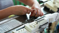 Woman straightens loops on knitting machine Stock Footage