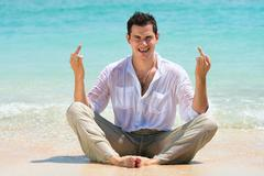 middle finger gesture by man on a beach - stock photo
