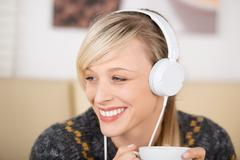 Blond woman listening music and drinking coffee Stock Photos