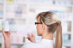 Female pharmacist picks up medicine form the shelf Stock Photos